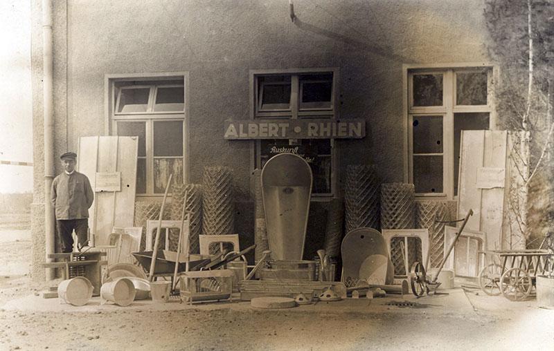 Abteilung der Firma Rhien auf dem Freigelände, Postkarte 1933 (Bernd Voigtländer). Auf dem Freigelände vor der Turnhalle präsentierte sich unter anderen die Eisenhandlung von Albert Rhien. Links im Bild der Firmeninhaber.